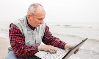 oude man met laptop op strand foto