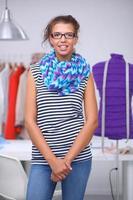 lachende modeontwerper permanent in de buurt van mannequin in kantoor foto