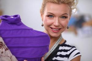 lachende modeontwerper vaststelling jurk op etalagepop in een studio foto