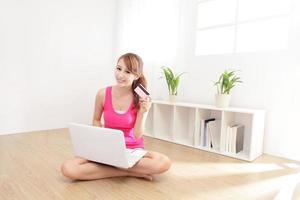 mooie vrouw winkelen met laptop en creditcard foto