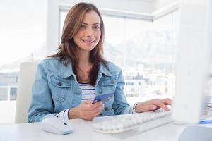 vrolijke vrouw die online met haar creditcard koopt foto
