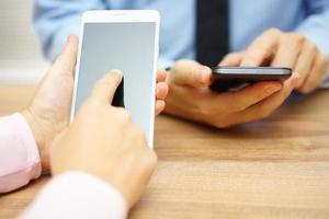 mensen uit het bedrijfsleven met behulp van slimme mobiele telefoons op kantoor foto