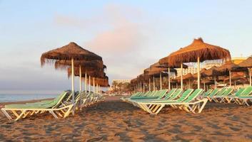 strand lounge stoel en parasol op eenzaam zandstrand. foto