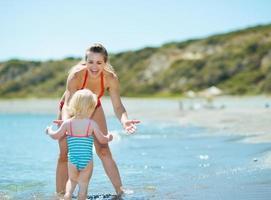 moeder en babymeisje spelen op Zeekust foto