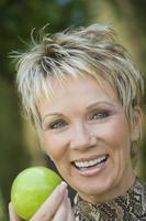 vrouw met appel buitenshuis, portret foto