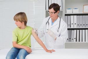 arts doet injectie bij kleine jongen foto