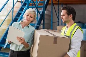 magazijnbeheerder en werknemer kijken naar klembord