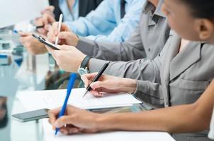 mensen uit het bedrijfsleven schrijven notitie in vergadering foto