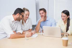 informeel commercieel team dat een vergadering heeft die laptop met behulp van foto