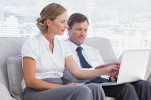 mensen uit het bedrijfsleven kijken iets op laptop