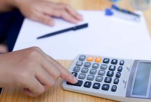zakenmensen werken hand op rekenmachine foto