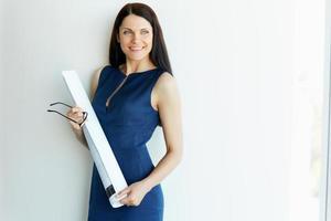 jonge vrouwelijke architect standind in een kantoor. mensen uit het bedrijfsleven foto