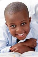 jonge jongen liggend op zijn bed glimlachen foto