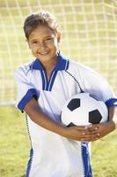 jong meisje, gekleed in voet bal kit permanent door doel foto