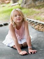 meisje geknield op trampoline foto