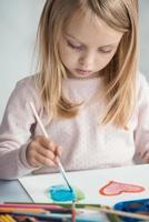 klein meisje tekent met penselen foto
