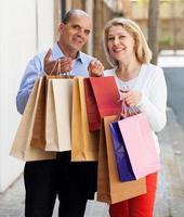 bejaarde echtpaar met boodschappentassen in handen en glimlachen