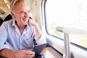 senior man leest e-boek over treinreis