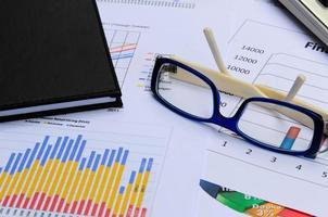 zakelijke grafieken en diagrammen met oogglas en boeknota foto