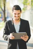 jonge Italiaanse jongen lopen met behulp van een tablet foto