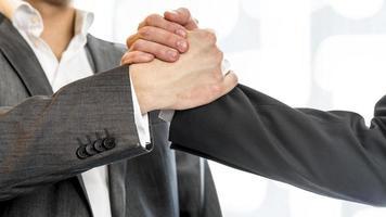 twee zakenlieden die hun handen in succes grijpen foto