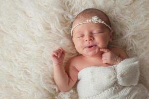 babymeisje draagt een witte gebreide muts foto