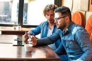 informele jongens in een café kijken naar mobiele telefoon foto