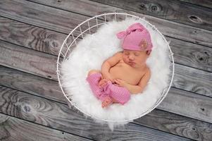 slapende pasgeboren babymeisje draagt roze slaapmuts foto