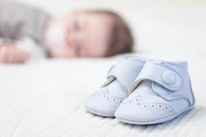 baby blauwe schoenen en babe slapen op achtergrond foto