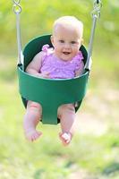 gelukkig babymeisje swingend op speelplaats foto