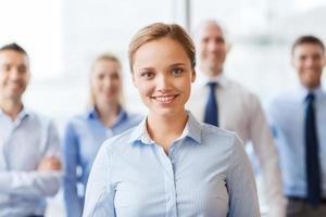 Glimlachende zakenvrouw met collega's in kantoor foto