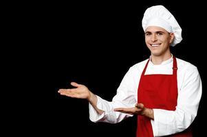 glimlachende mannelijke chef-kok die iets voorstelt foto