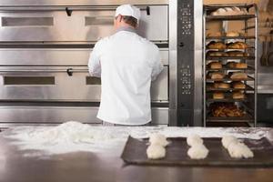 bakker die de oven opent om het deeg in te doen foto