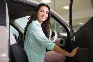 lachende vrouw zitten achter het stuur van haar nieuwe auto foto