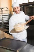 gelukkig bakker vers brood uit te nemen foto