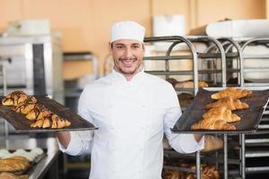 lachende bakker met dienbladen met croissants