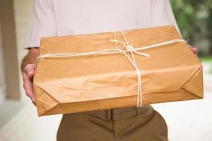 sluit omhoog van de leveringsmens die pakket geeft