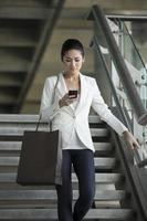 Aziatische zakenvrouw het lezen van berichten op de telefoon tijdens het wandelen