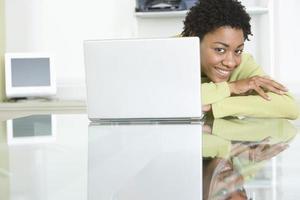 Glimlachende zakenvrouw met laptop op tafel foto