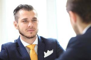 jonge manager die naar de uitleg van zijn collega luistert foto
