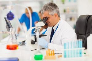 senior medisch onderzoeker kijkt door de microscoop foto