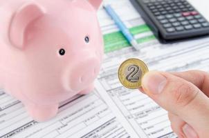 hand met Poolse munt. Poolse inkomstenbelastingformulieren foto