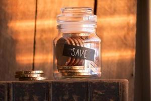 idee opslaan, gouden munten in een glazen pot foto