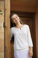 glimlachende vrouw die zich op de drempel bevindt foto