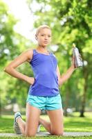 vrouwelijke atleet waterfles houden en rusten in een park foto