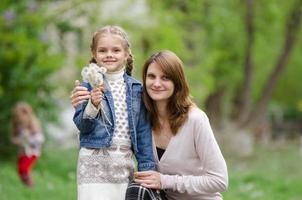 jonge vrouw omhelst haar dochter met paardebloemen foto