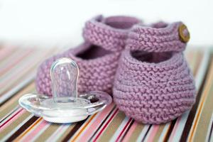 handgemaakte babyschoentjes en een fopspeen foto