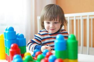 peuter jongen speelt plastic blokken foto
