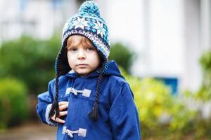 portret van schattige peuter jongen lachend op koude winterdag. foto