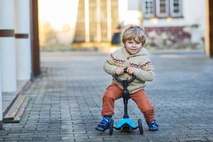 kleine peuter jongen rijden en zijn scooter fiets in de zomer foto